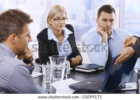 Businesspeople looking at laptop computer at meeting.? - stock photo