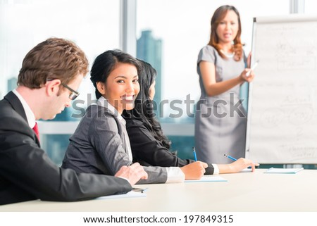 Businesspeople making notes in a meeting - stock photo