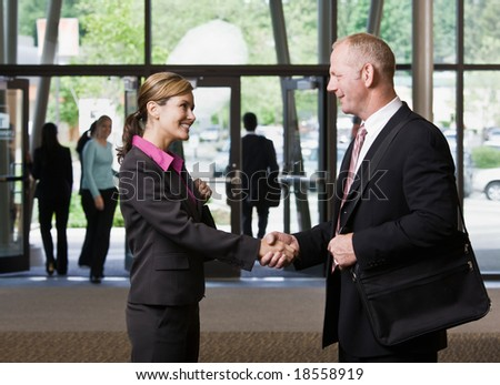 Businesspeople meeting and shaking hands in office lobby - stock photo