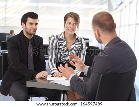 Businesspeople meeting at table in office lobby, talking, smiling. - stock photo