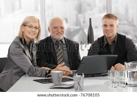 Businesspeople meeting with senior executive, sitting at table, smiling at camera.? - stock photo