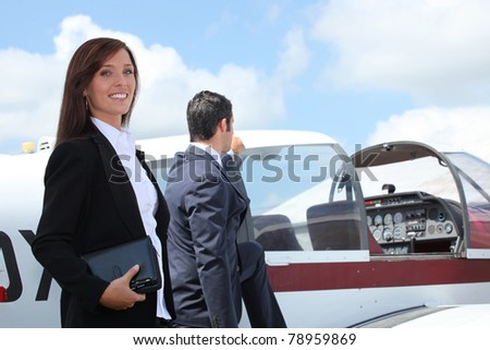 Businesspeople next to airplane - stock photo