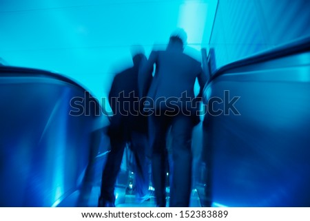 businesspeople on escalator in motion - stock photo