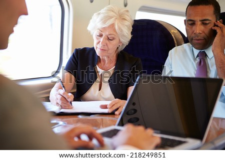 Businesspeople On Train Using Digital Devices - stock photo