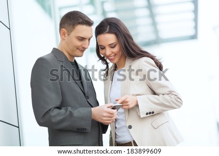Businesspeople outdoor looking at smart phone and smiling. - stock photo