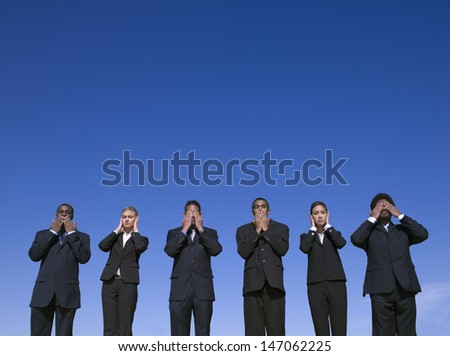"Businesspeople outdoors motioning ""hear no evil, see no evil, speak no evil"" - stock photo"
