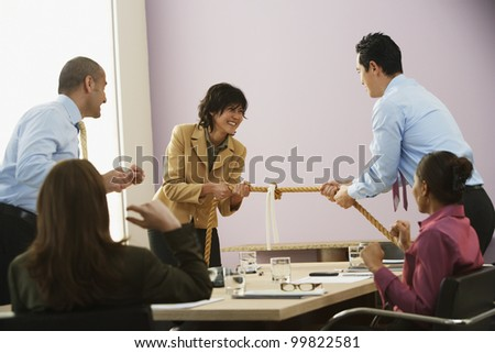 Businesspeople playing tug of war - stock photo