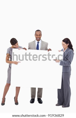 Businesspeople pointing at blank sign in their hands against a white background - stock photo