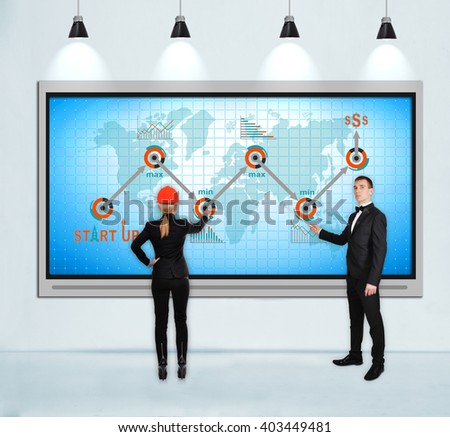 businesspeople pointing to tv screen with start up concept - stock photo