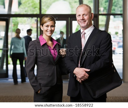 Businesspeople posing in office lobby - stock photo