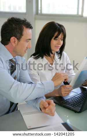 Businesspeople reviewing paperwork - stock photo