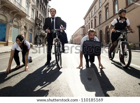 Businesspeople riding on bikes and running in city - stock photo