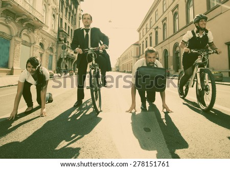 Businesspeople riding on bikes and running in city - retro style photograph - stock photo
