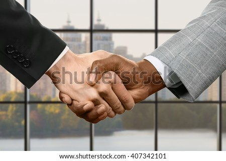 Businesspeople shake hands. Business handshake on daytime background. Our negotiations were successful. In the name of progress. - stock photo