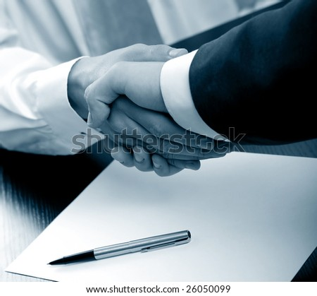 Businesspeople shaking hands. blue tone - stock photo