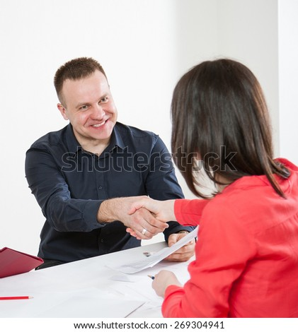 Businesspeople shaking hands each other on workplace - stock photo