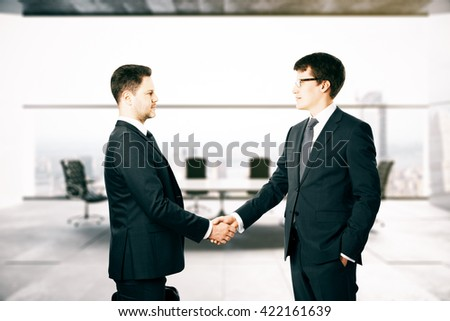 Businesspeople shaking hands in blurry conference room interior - stock photo