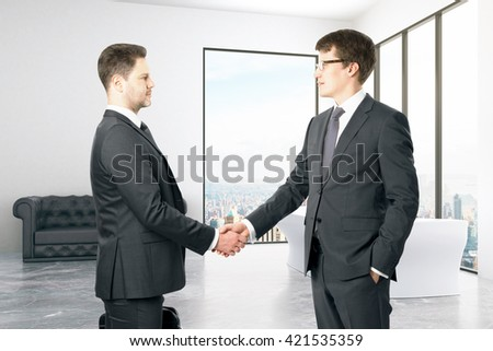 Businesspeople shaking hands in interior with city view - stock photo