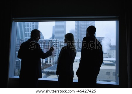 Businesspeople silhouetted in front of a large window that overlooks the city. Horizontal shot. - stock photo