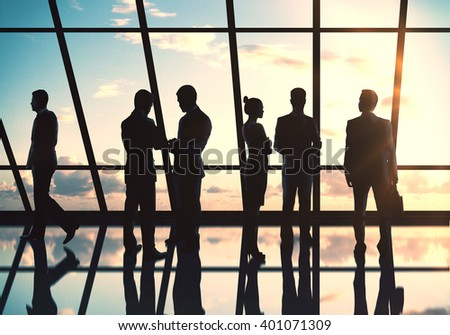 Businesspeople silhouettes standing against panoramic office window - stock photo