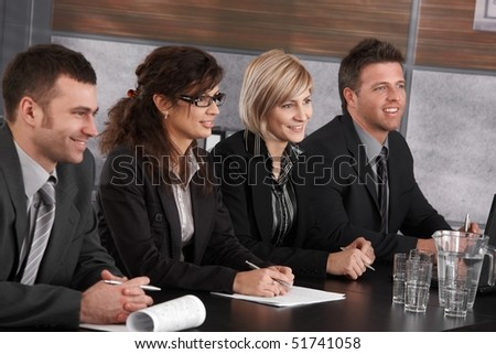 Businesspeople sitting at conference table on business seminar, smiling. - stock photo