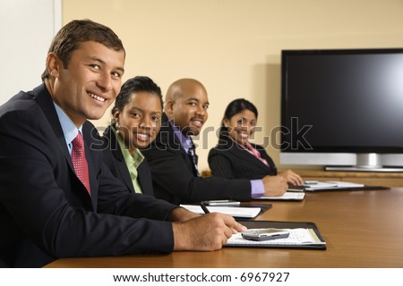 Businesspeople sitting at conference table smiling with flat screen display in background.