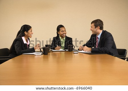 Businesspeople sitting at conference table talking and smiling. - stock photo