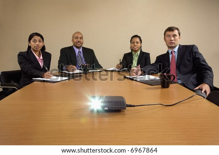 Businesspeople sitting at conference table  watching LCD projector presentation.