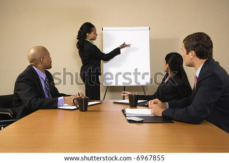 Businesspeople sitting at conference table  while businesswoman gives presentation.
