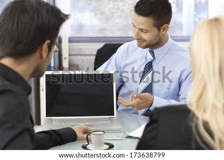 Businesspeople sitting at desk in office around open laptop with blank screen. - stock photo