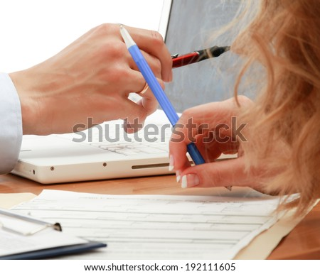 Businesspeople sitting at desk working in team together with documents - stock photo