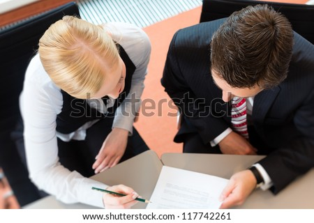 Businesspeople sitting at office desk with a document and laptop - stock photo
