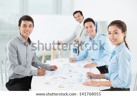 Businesspeople sitting at the meeting and looking at camera - stock photo