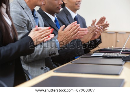 Businesspeople sitting in a row and applauding - stock photo