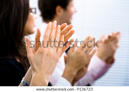 Businesspeople sitting in a row and applauding. Close-up on hands. - stock photo