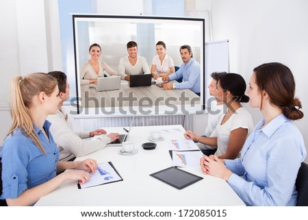 Businesspeople Sitting In Conference Room Looking At Projector Screen - stock photo