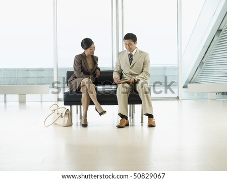 Businesspeople Sitting on Bench in airport looking over documents - stock photo