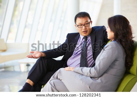 Businesspeople Sitting On Sofa In Modern Office - stock photo