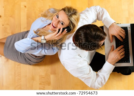 Businesspeople sitting on the floor at home working with laptop computer and telephone - stock photo