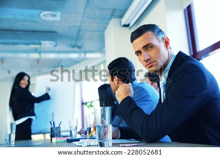 Businesspeople sitting on the meeting while businesswoman presenting something - stock photo