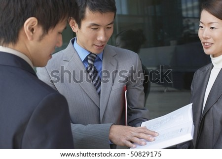 Businesspeople standing outside, looking over documents