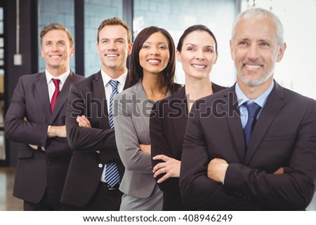 Businesspeople standing with arms crossed in office - stock photo