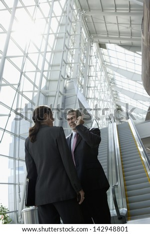 Businesspeople talking in airport - stock photo