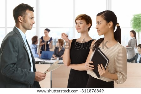 Businesspeople talking in busy office, diverse group of people.