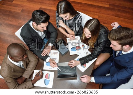 Businesspeople, teamwork. Group of multi-ethnic busy people working in an office. Top view - stock photo