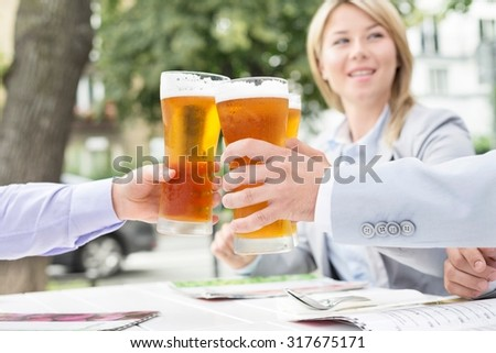 Businesspeople toasting beer glasses at outdoor restaurant - stock photo