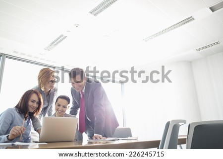 Businesspeople using laptop at conference table