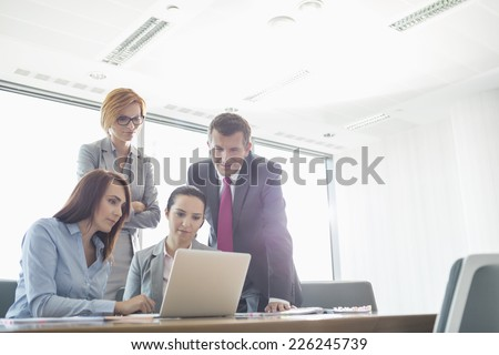 Businesspeople using laptop in conference room