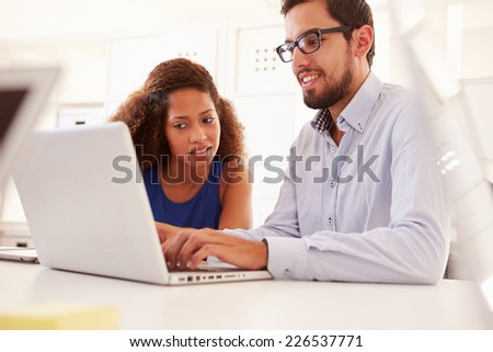 Businesspeople Using Laptop In Office Of Start Up Business - stock photo