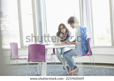 Businesspeople using laptop together in creative office - stock photo